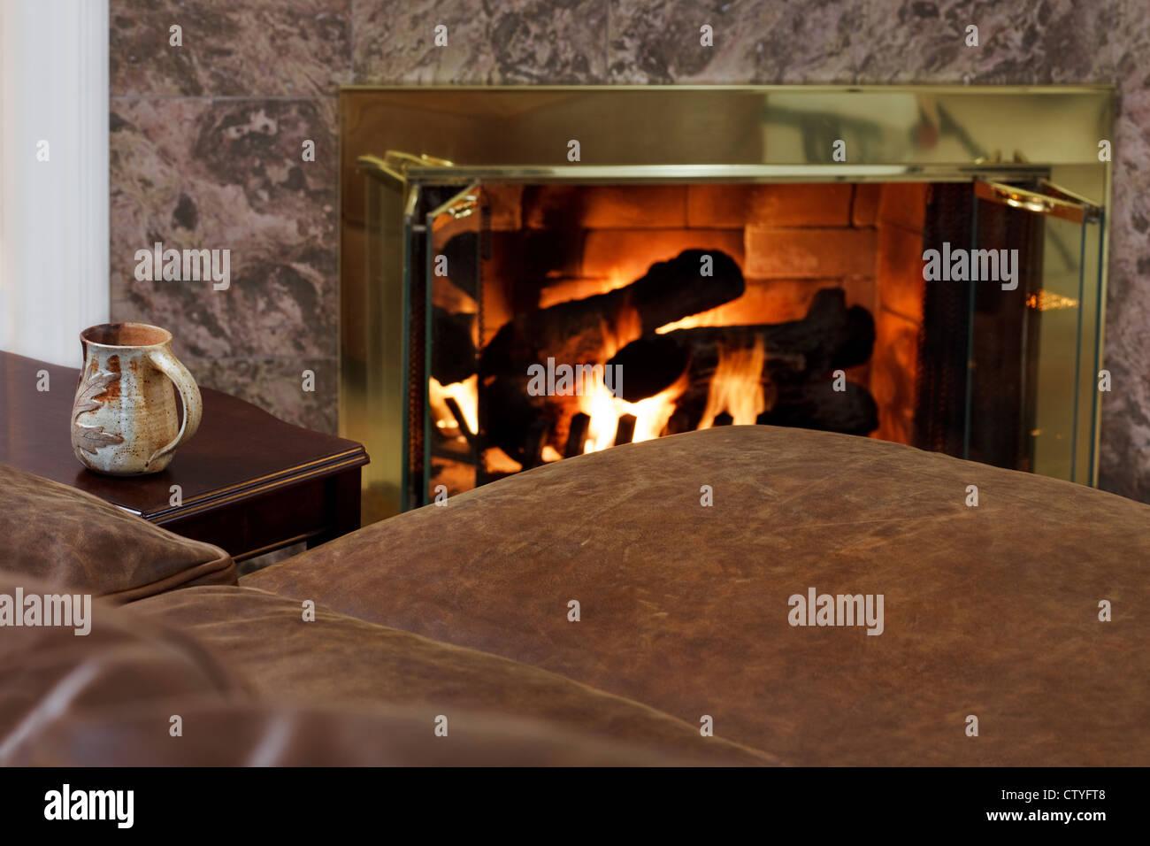 Coffee mug & comfy sofa by the fire - Stock Image