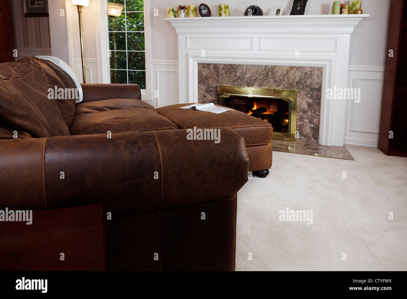 Comfy sofa & ottoman to read by the living room fire - Stock Image