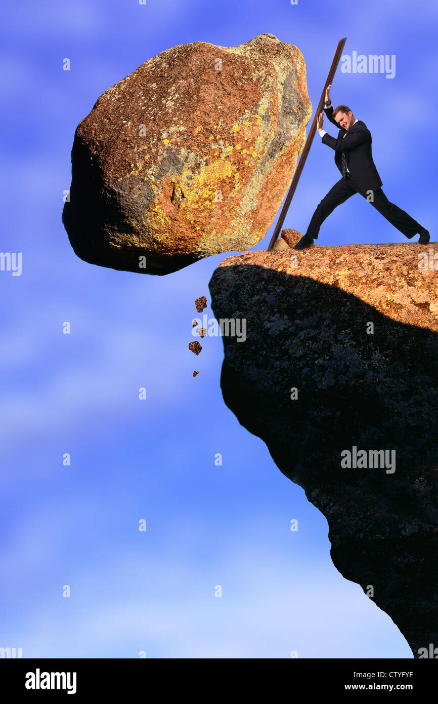 Businessman pushing rock off cliff Stock Photo - Alamy