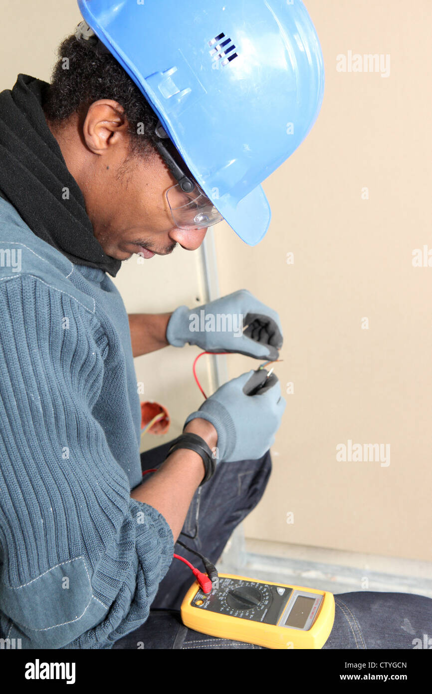Electrician using voltmeter - Stock Image
