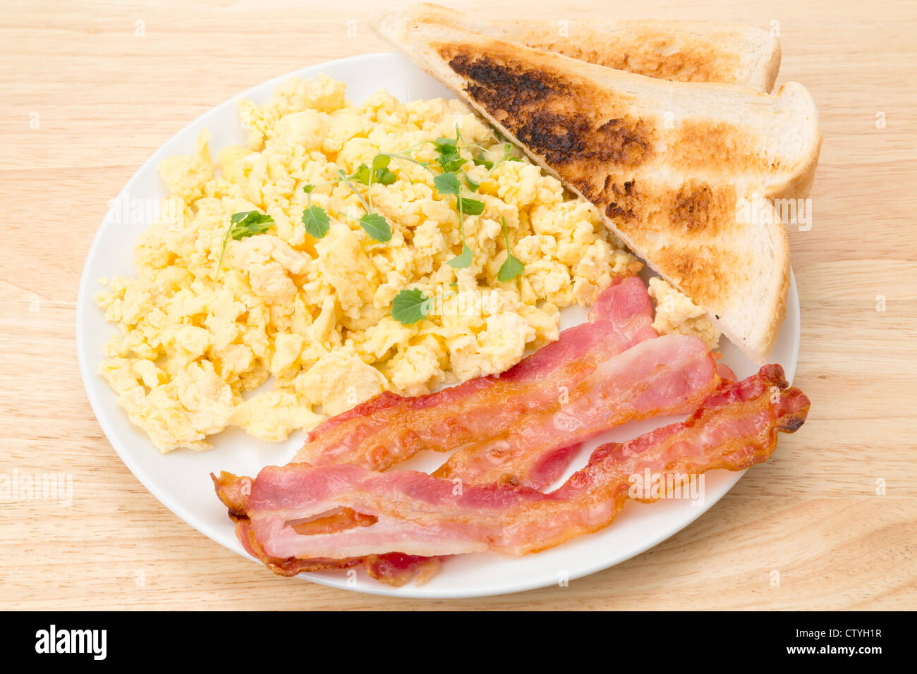 Breakfast of scrambled eggs with streaky bacon and slices of toasted bread - studio shot - Stock Image
