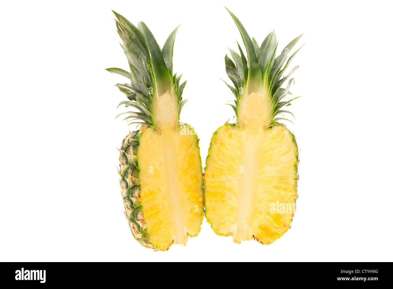 Fresh pineapple cut in half - studio shot with a white background - Stock Image
