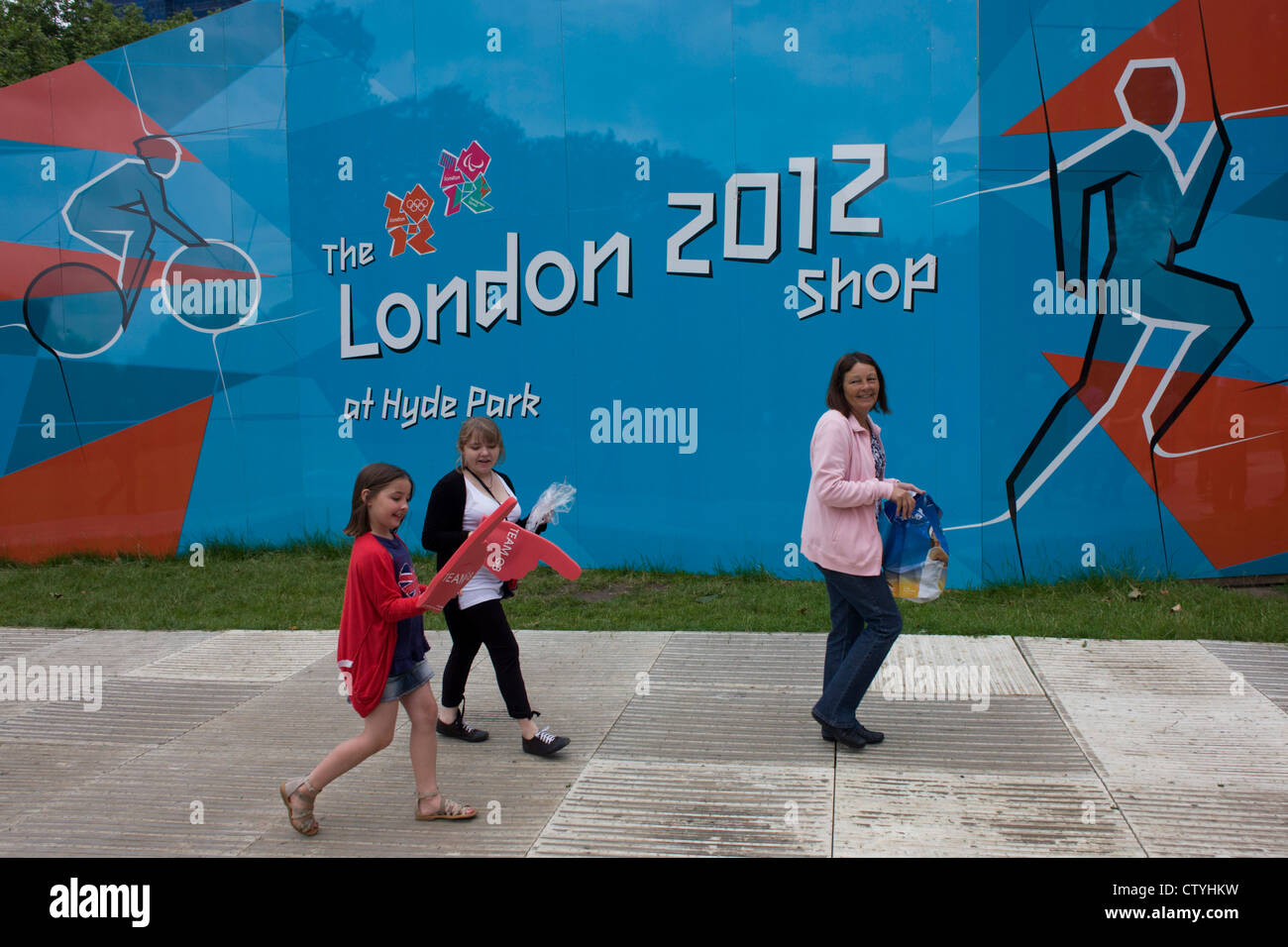 Young girls enjoy their latest purchase of foam hands as they exit the official London 2012 merchandise shop - hours - Stock Image