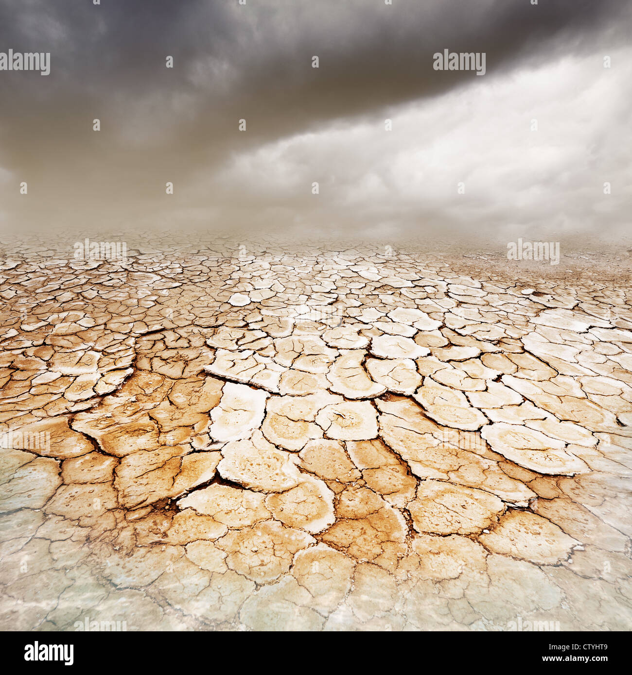 Dry, parched cracked earth with stormy dusty sky and foreground water - Stock Image