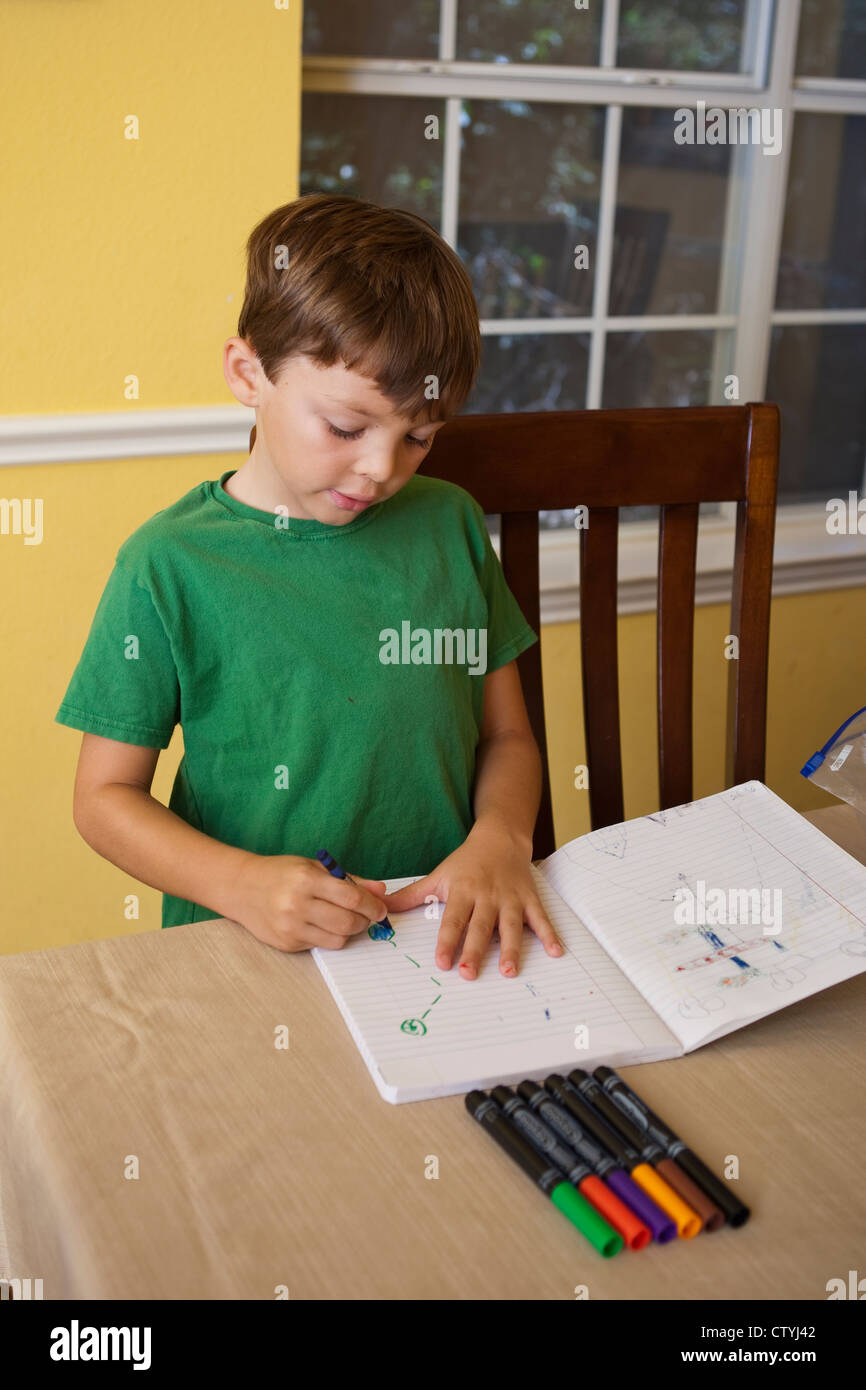 7 and 8 year old Mexican-American boy snacks on junk food, Cheetos, while drawing at home with markers. - Stock Image