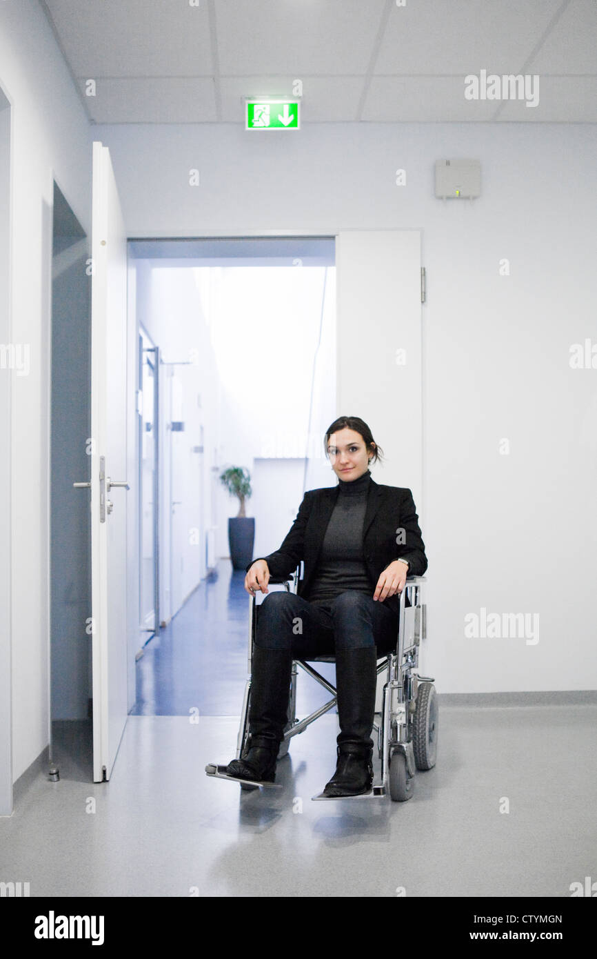 Young disabled woman on wheelchair in hospital environment - Stock Image