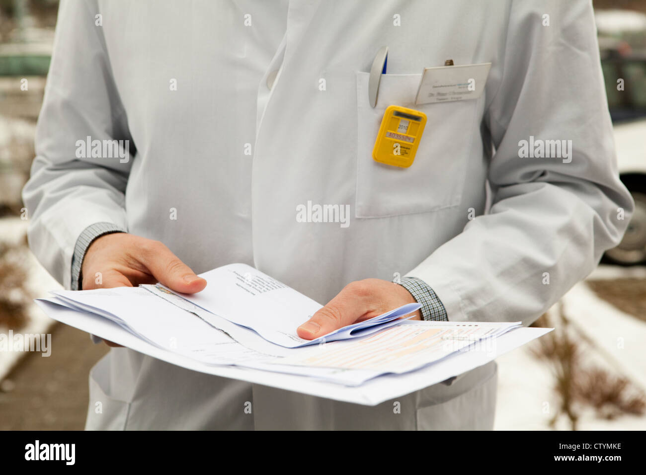 Radiologist wearing a dosimeter on his lapel - Stock Image