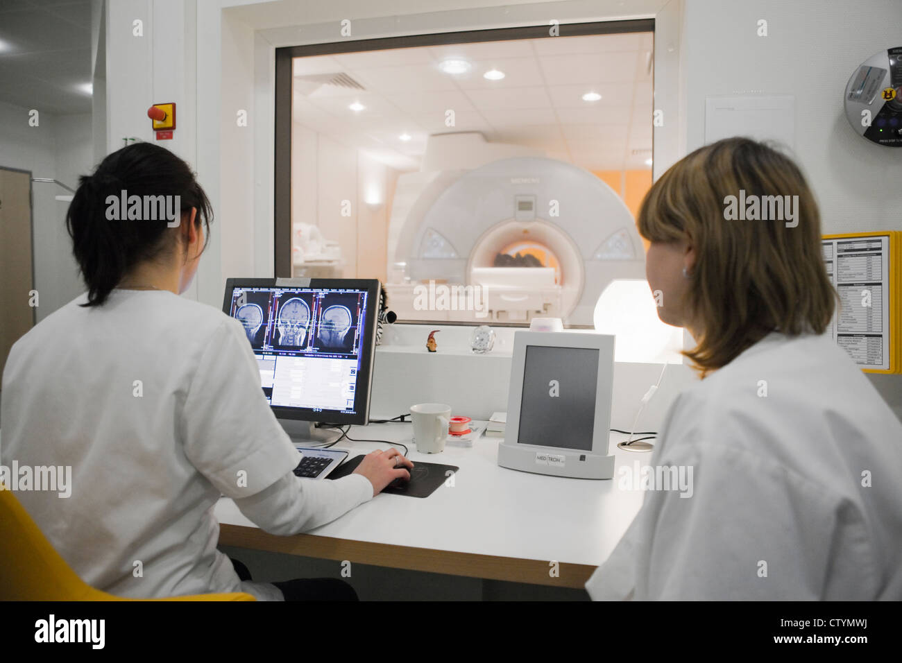 Female doctor and technician during a MRI brain scan - Stock Image