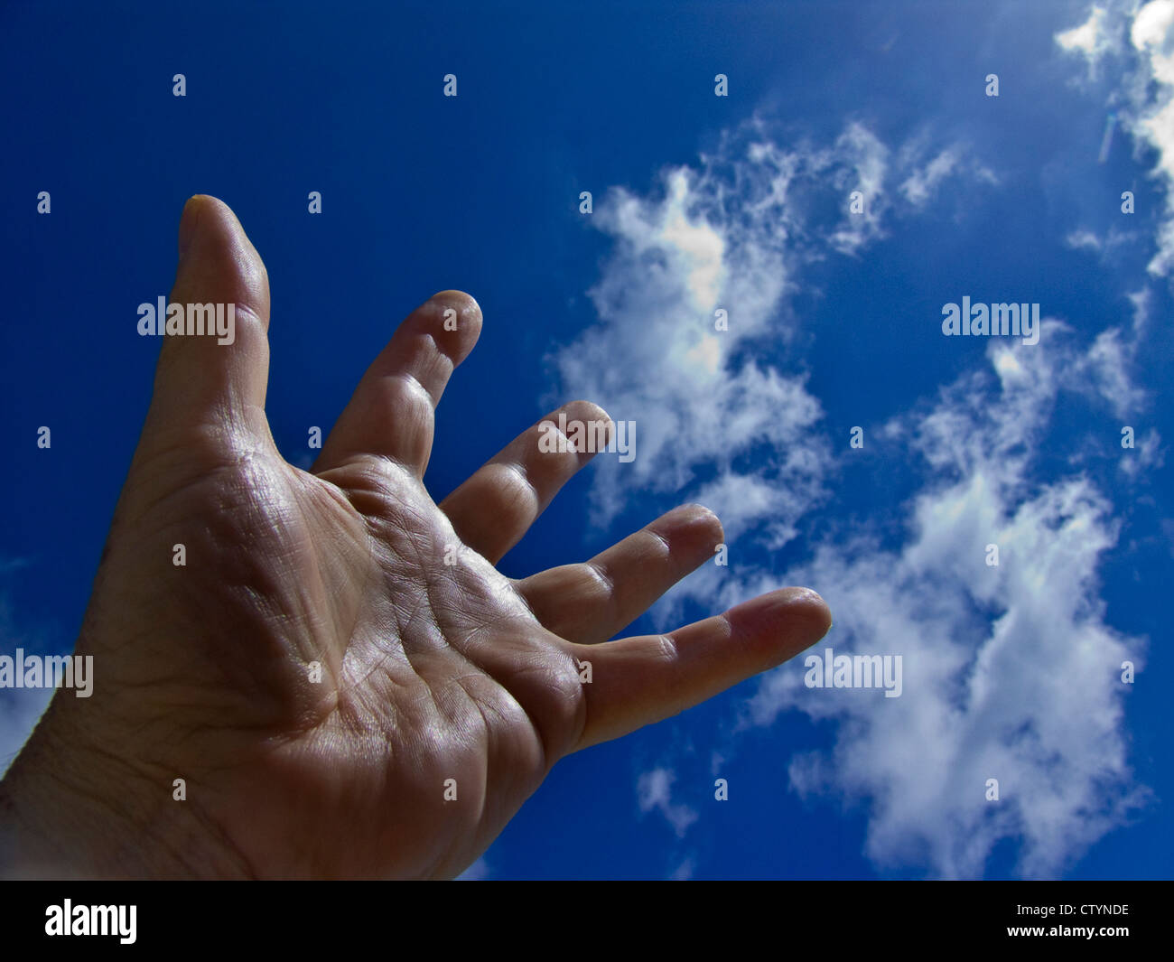 Male hand stretches imploringly up to the sky Stock Photo