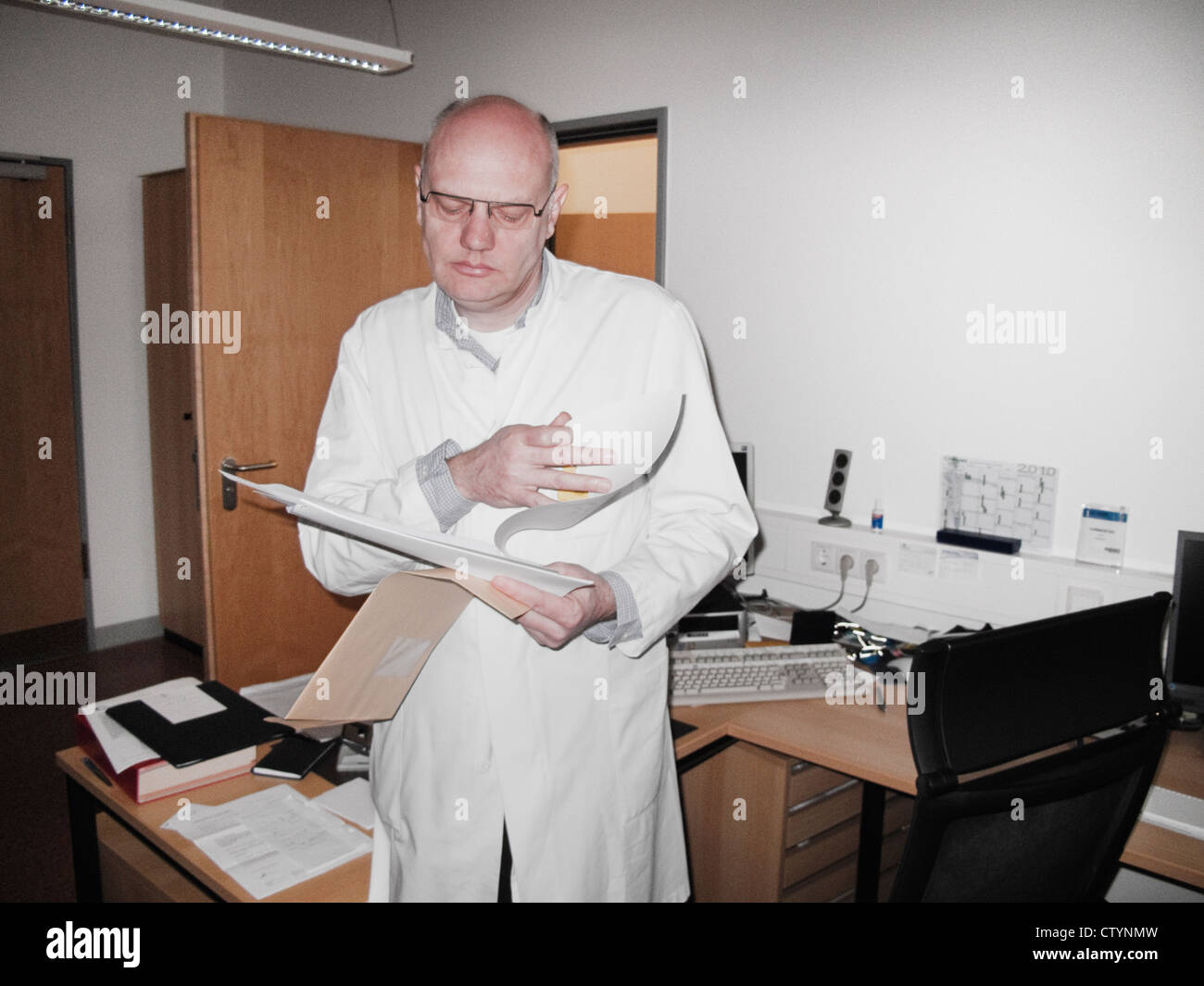 Doctor looking at paperwork in his office - Stock Image