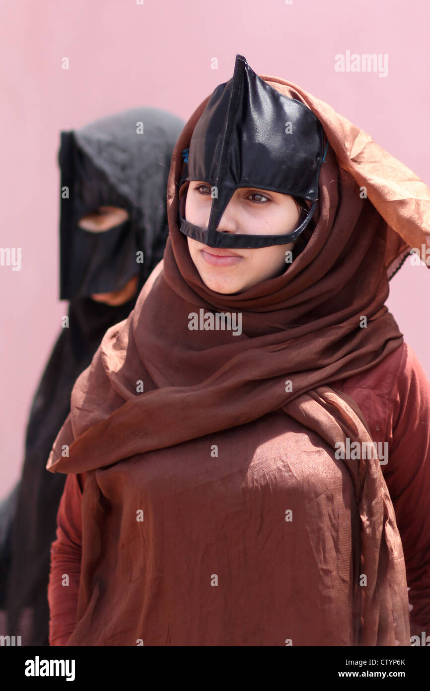 young muslim woman with traditional mask and clothing - Stock Image