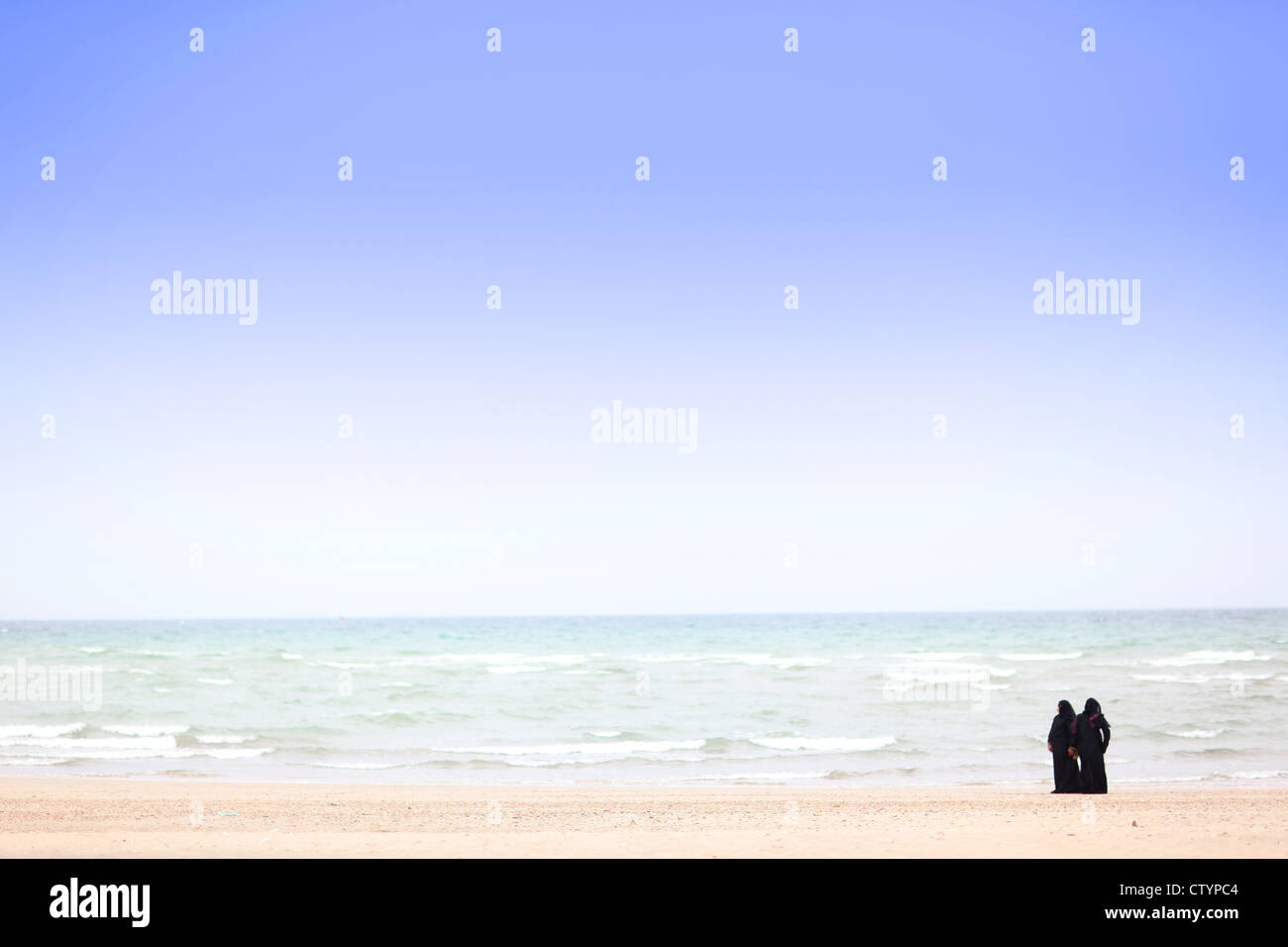 Muslim women near the sea - Stock Image