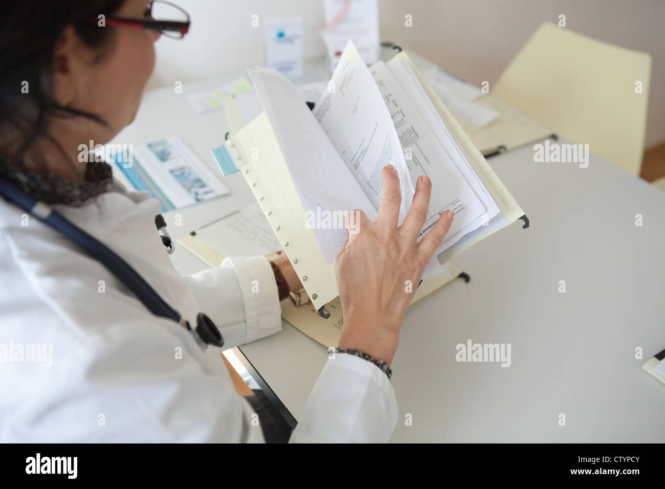 Female doctor  sorting out paperwork - Stock Image