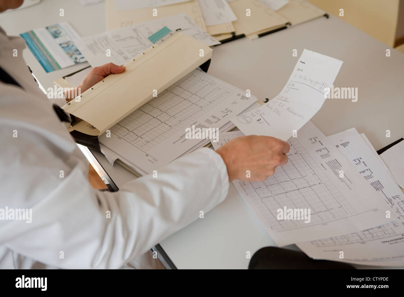 Doctor sorting-out paperwork-close-up - Stock Image