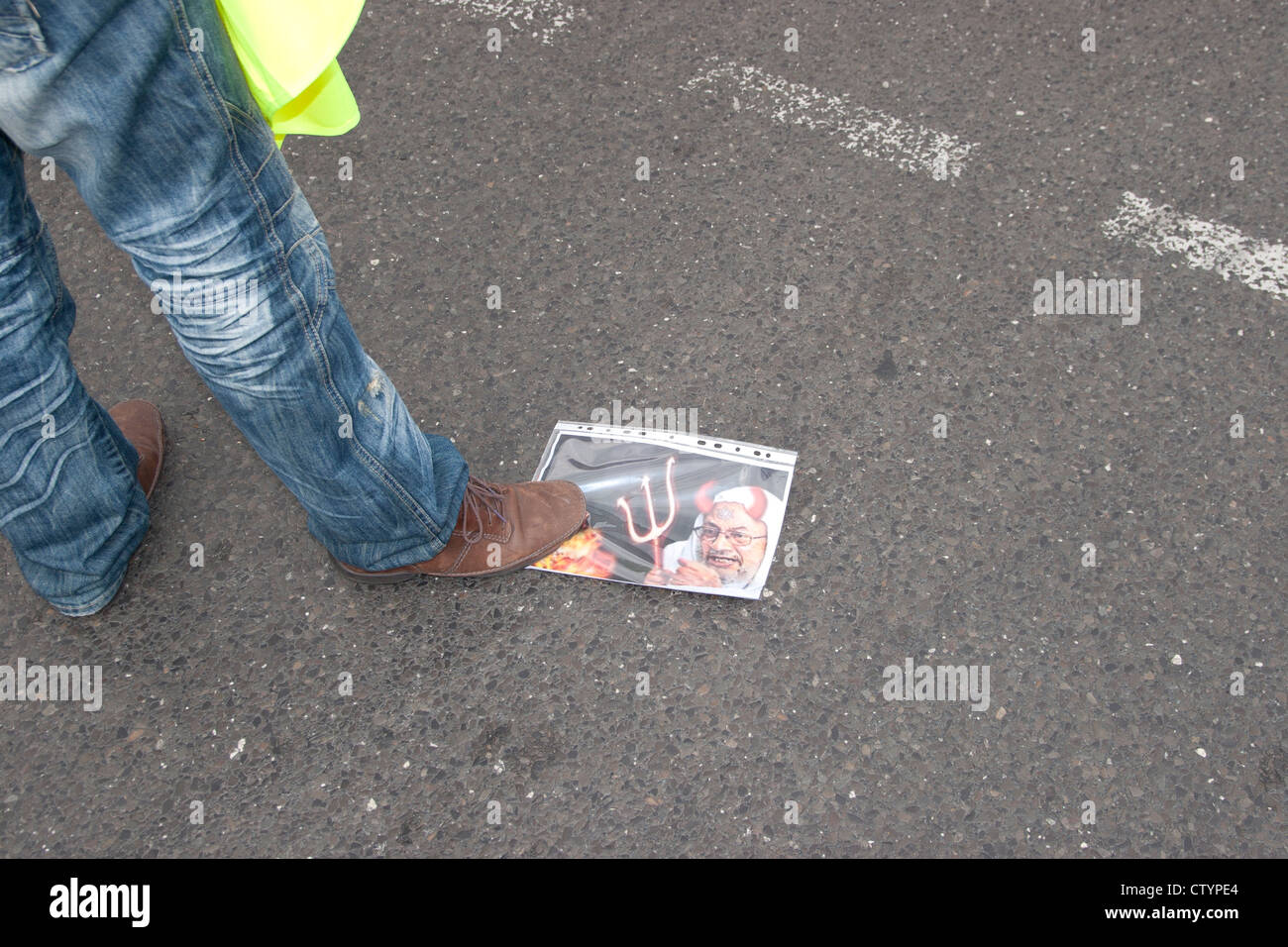 Pro Assad demonstration in Berlin. An Assad loyalist stamps on a picture showing  Yusuf al-Qaradawi. - Stock Image
