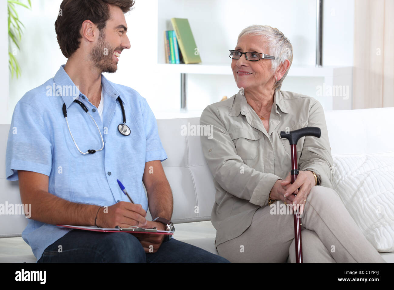 Senior woman talking to a young medic - Stock Image