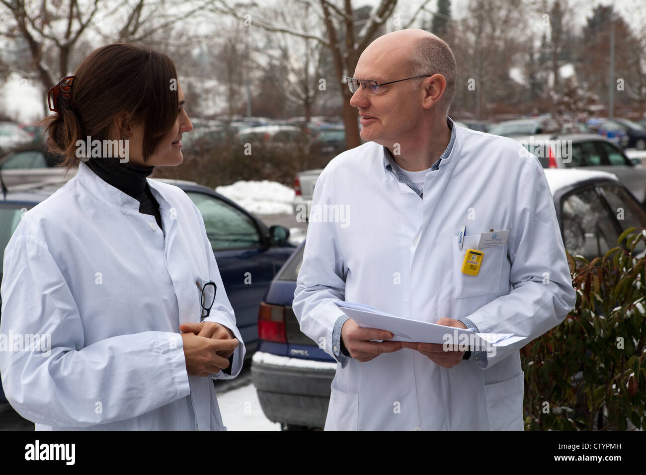 Older doctor having a conversation with younger female colleague - Stock Image