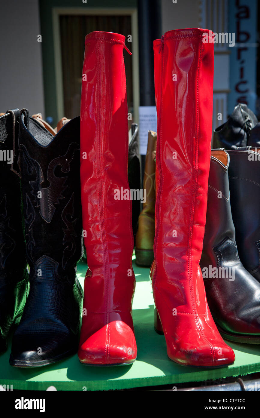 Color photograph of boots at a street fair. Red boots prominent. - Stock Image