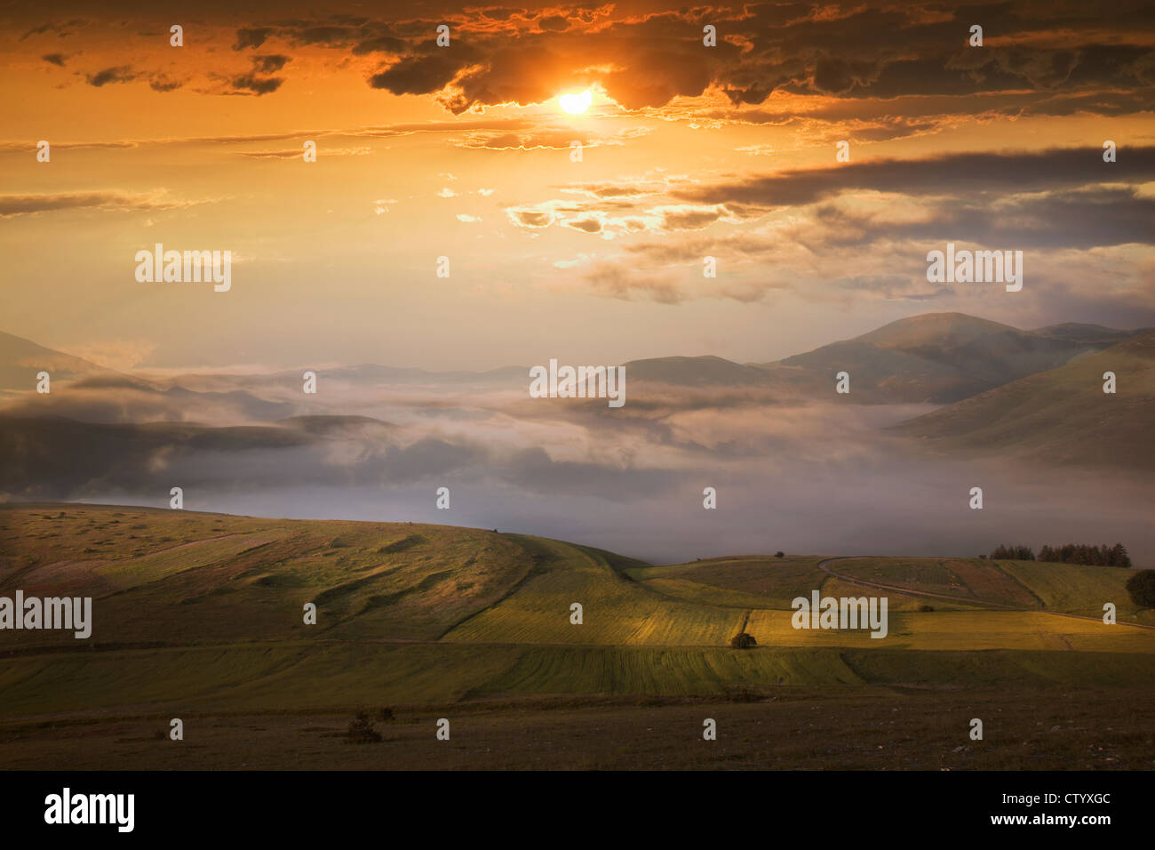 Sunset in dramatic sky over fields - Stock Image