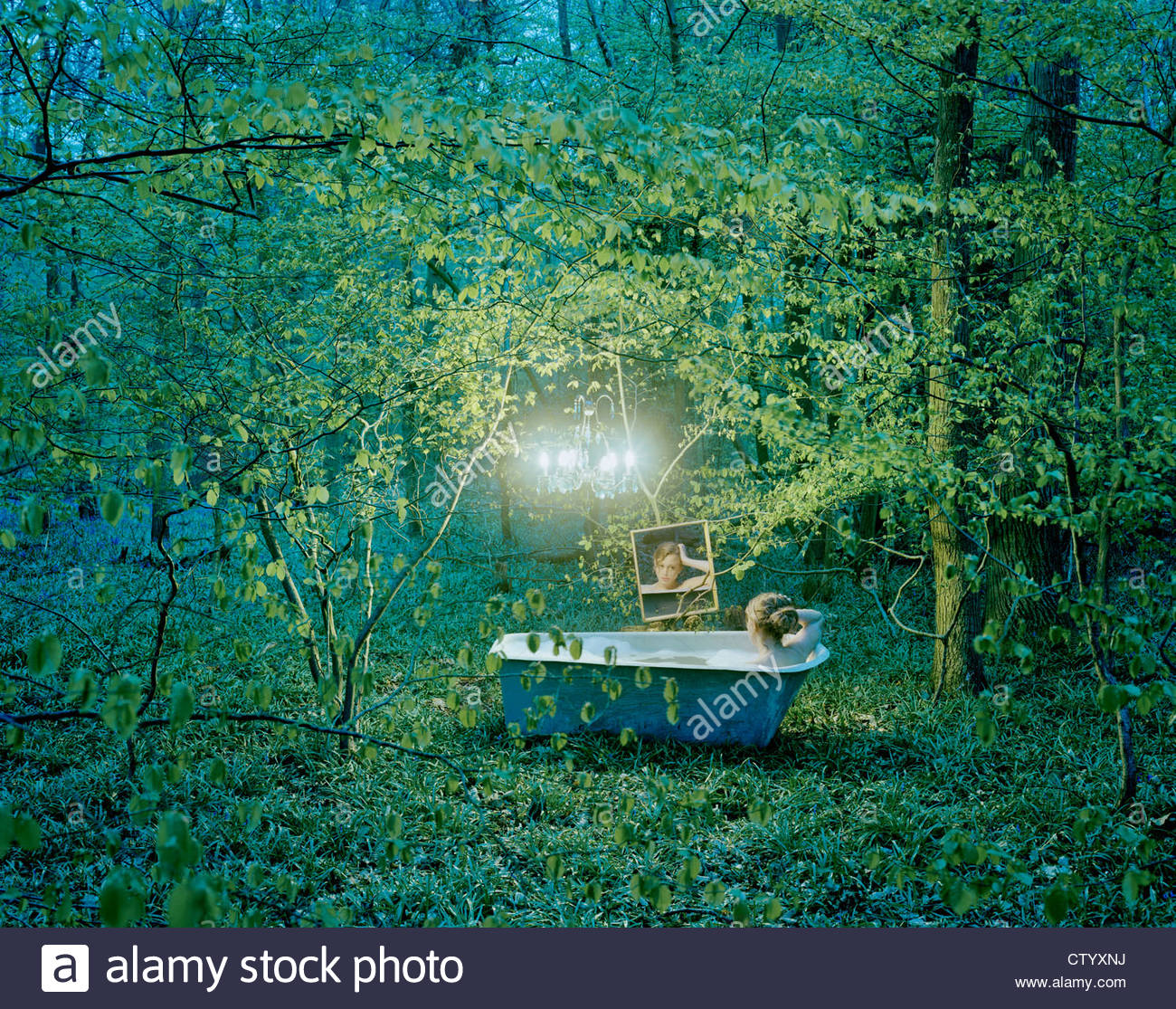 Woman bathing with mirror in forest - Stock Image