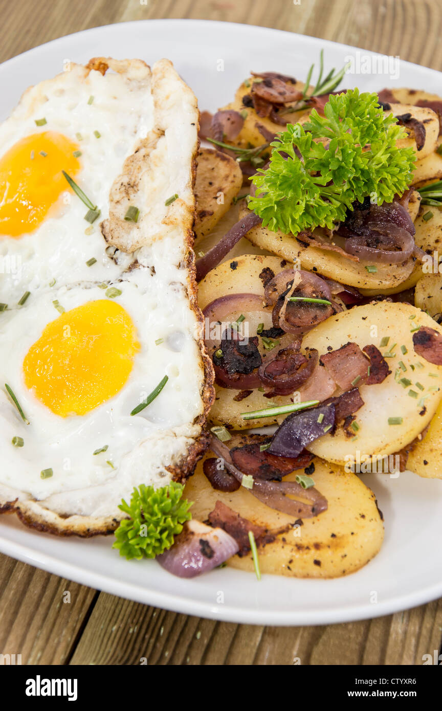 Fried Egg on a heap of roasted Potatoes on wooden background Stock Photo