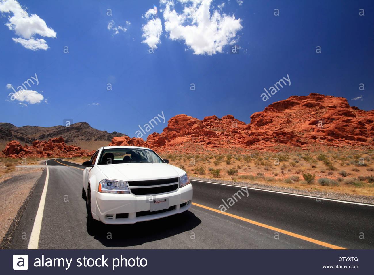Car driving on desert road - Stock Image