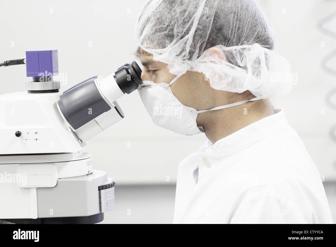 Scientist using microscope in lab - Stock Image