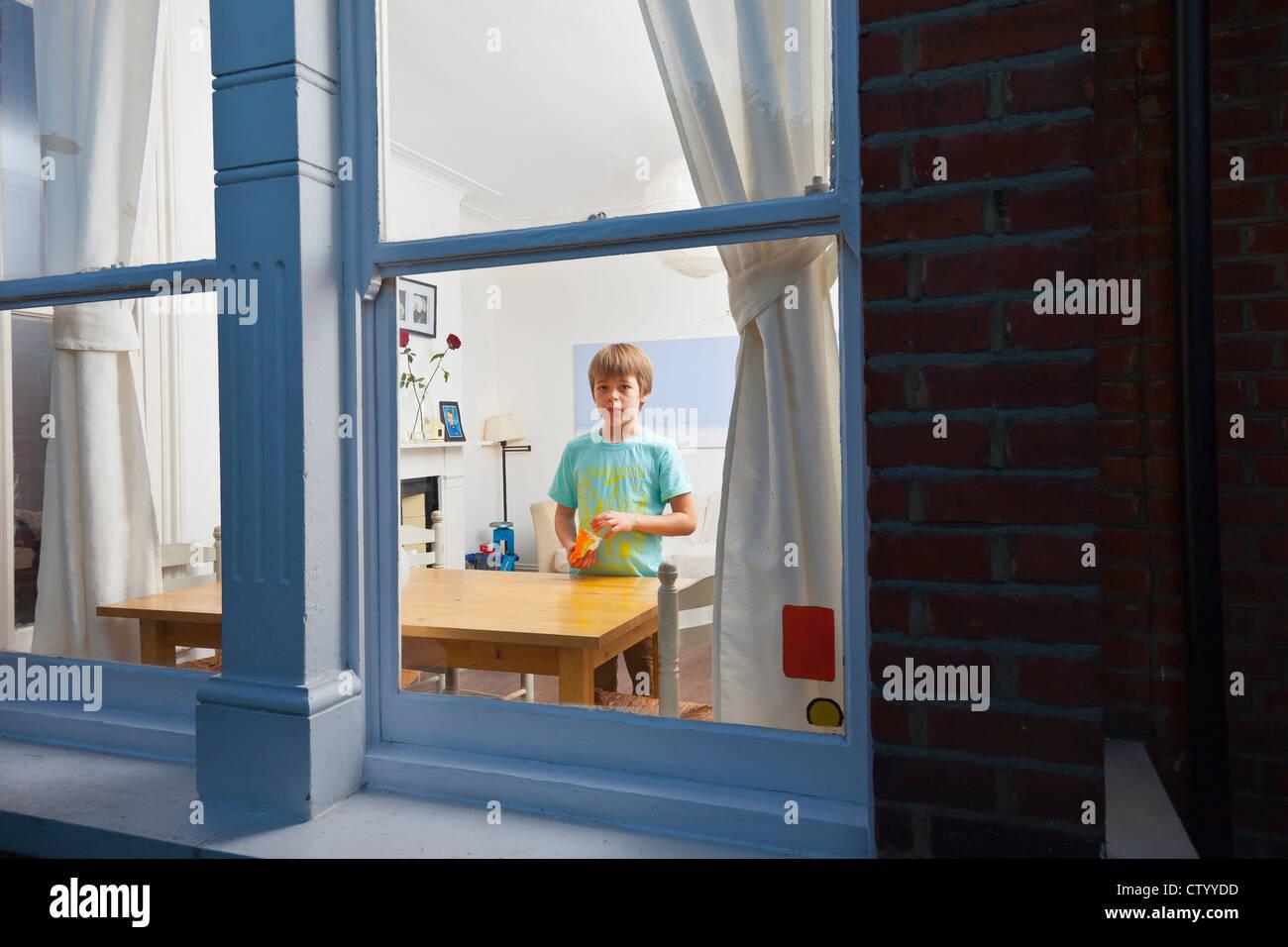 Boy in living room viewed through window - Stock Image