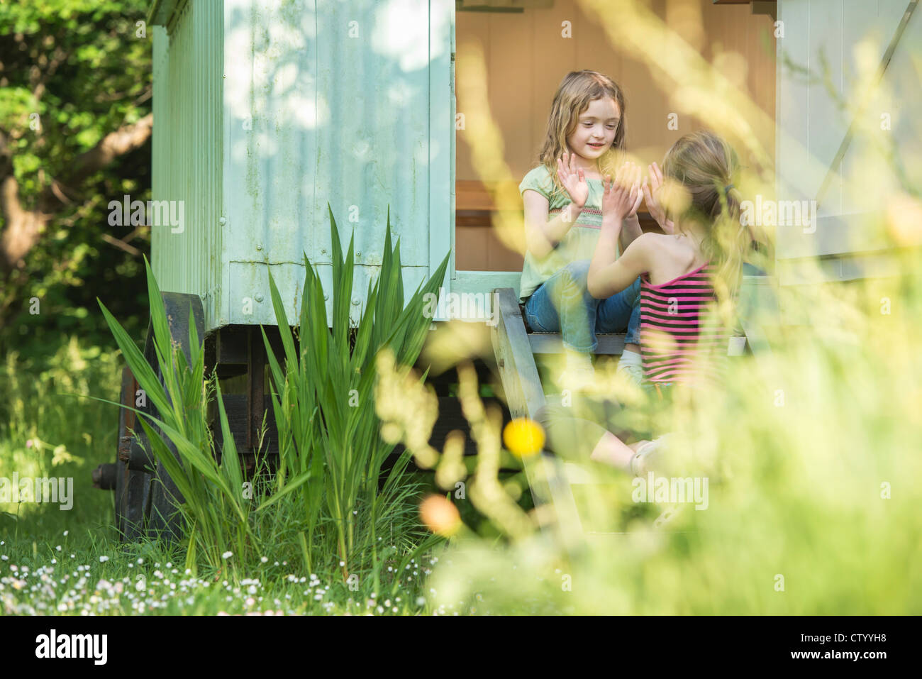 Girls playing together in doorway - Stock Image