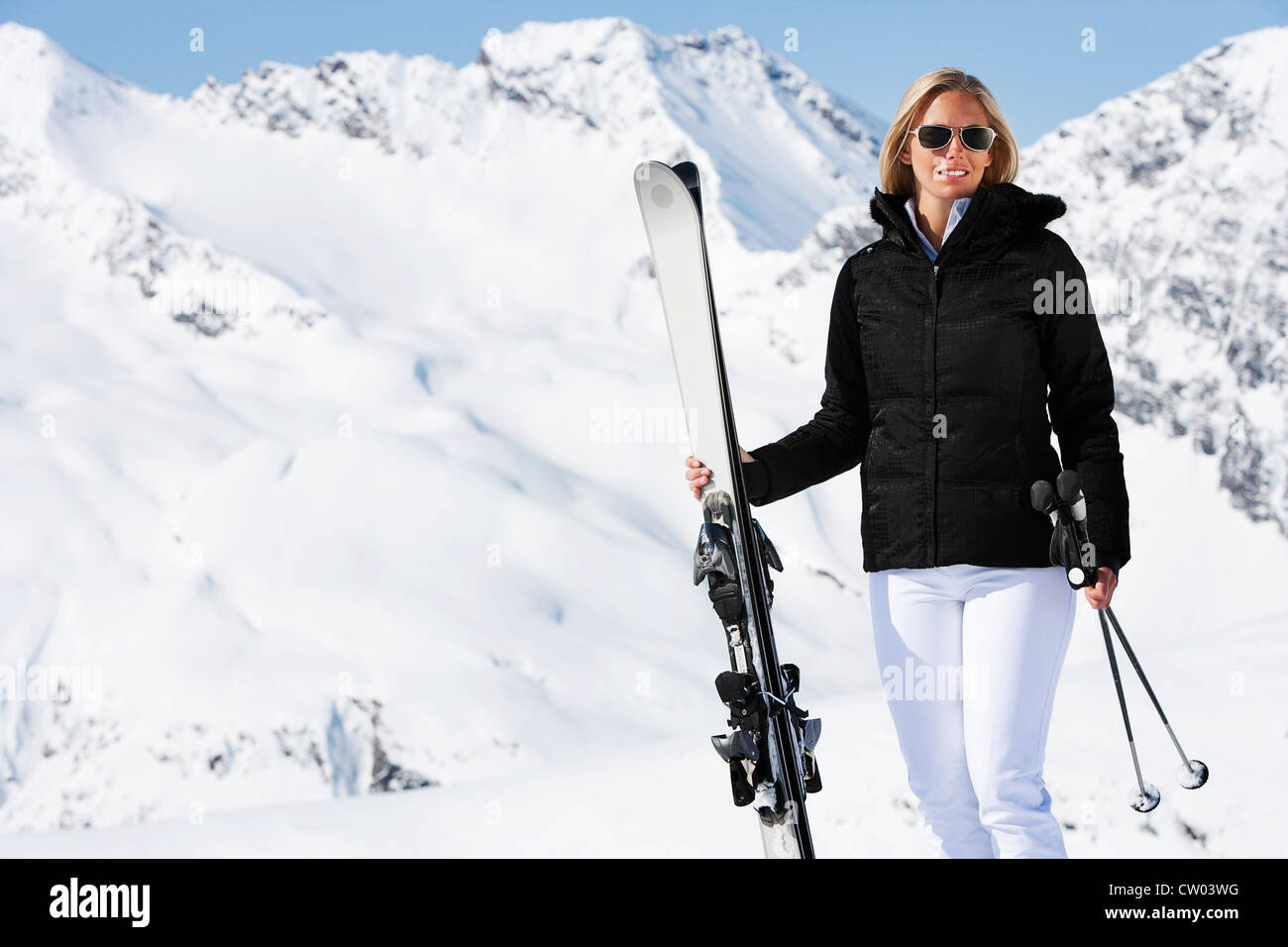 Skier standing on snowy mountain - Stock Image