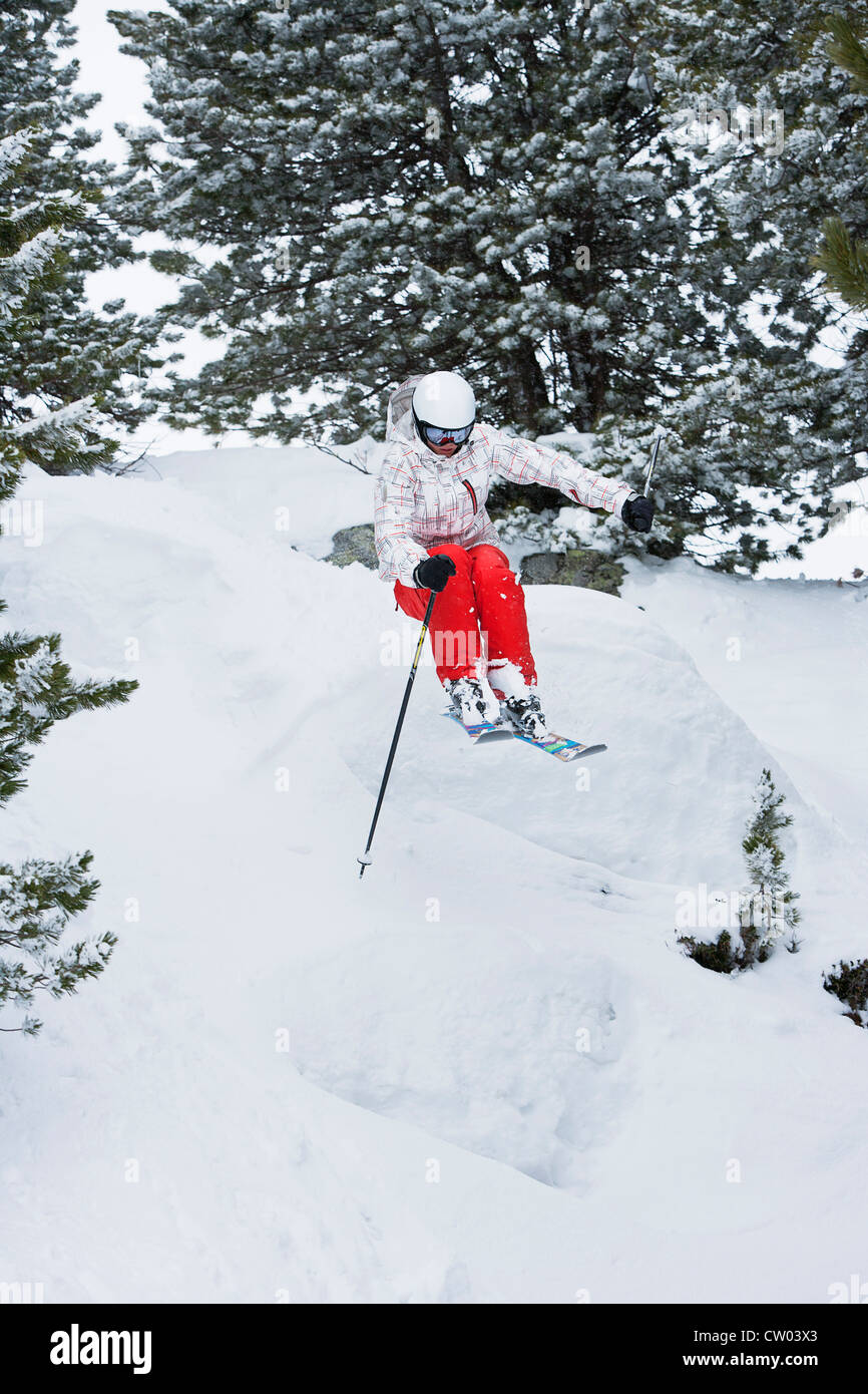 Skier jumping on snowy slope - Stock Image