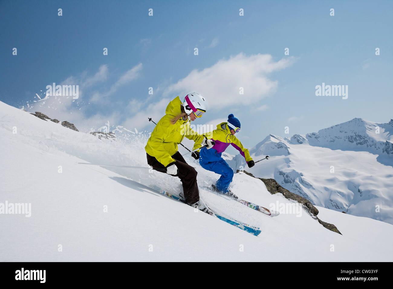 Skiers coasting on snowy slope - Stock Image
