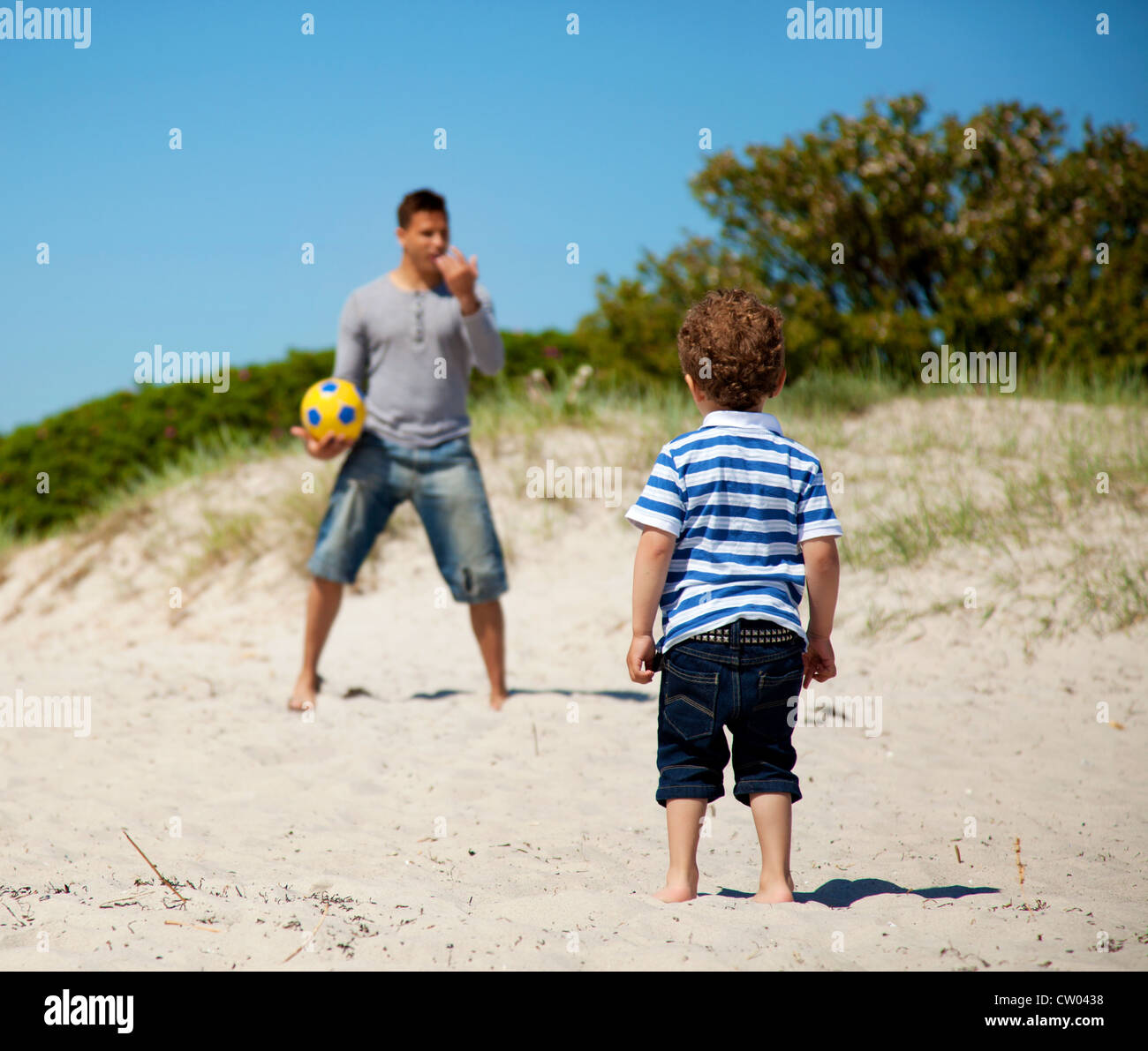 Child looking at his dad teaching him how to play soccer outdoors - Stock Image