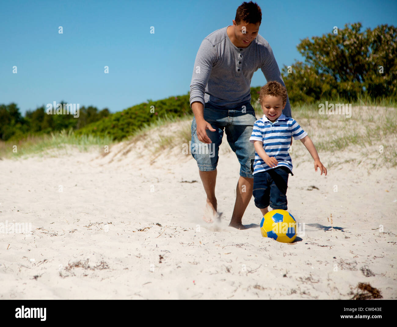 Father and son enjoying a soccer game on the beach - Stock Image