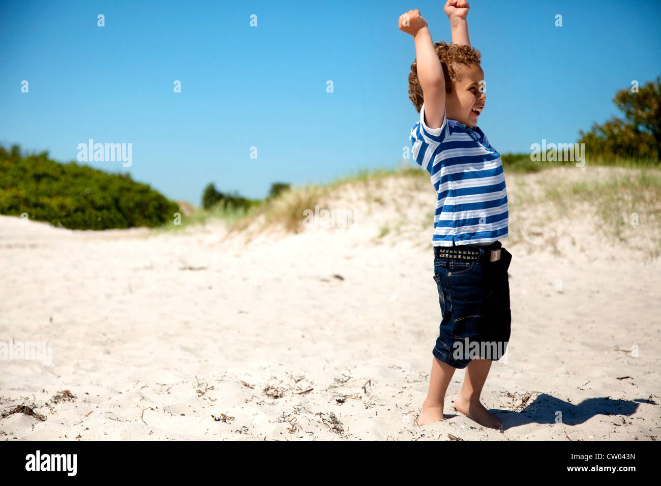 Young boy with arms stretched looks happy as he plays on the sand - Stock Image