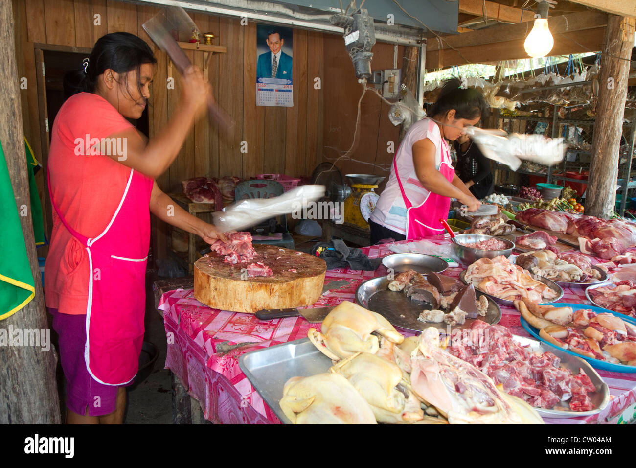 Women chopping and selling meat at an open air market on the island of Ko Samui, Thailand. - Stock Image