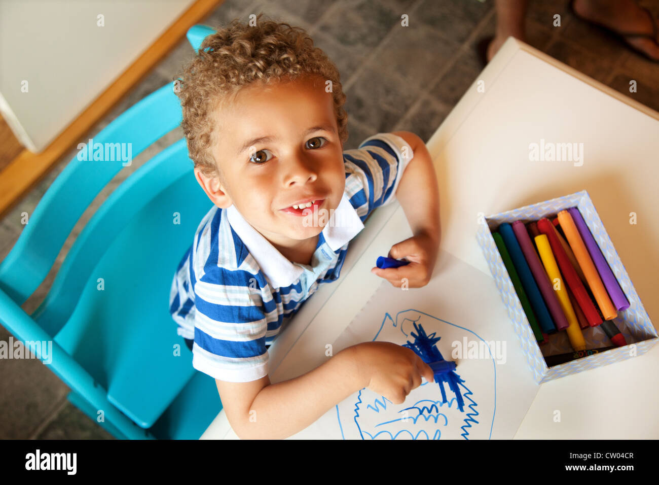 Charming Little Kid Looking Up And Playing With Crayons
