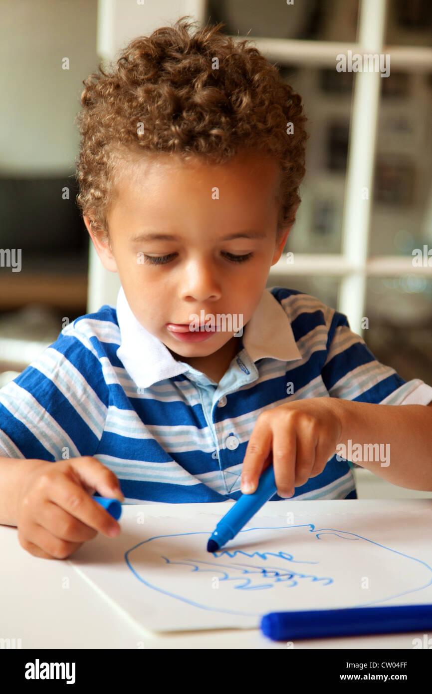 Portrait of a preschooler looking happy after finishing his homework - Stock Image