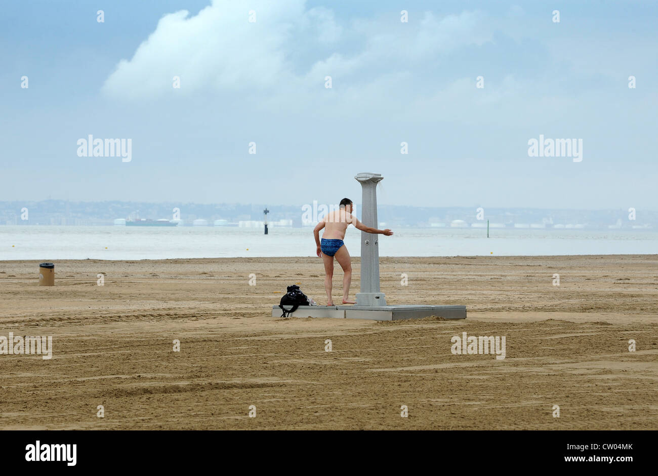 Man taking a shower on a deserted beach at Deauville France - Stock Image