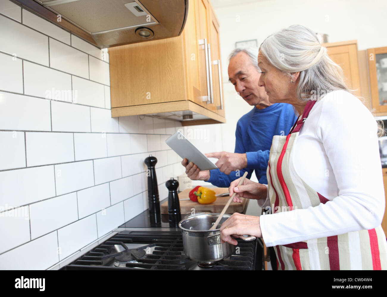 Older couple cooking together in kitchen - Stock Image