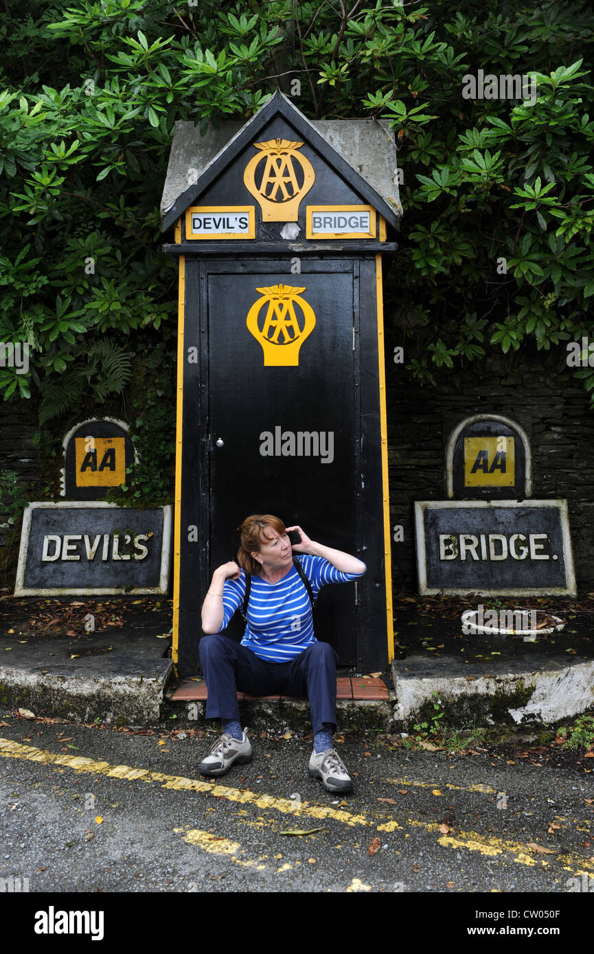 Woman using mobile phone next to AA phone box Devil's Bridge Wales Uk - Stock Image