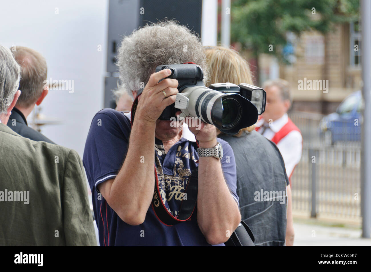 Mature adult Caucasian man with gray curly hair, professional male photographer, taking pictures with a full frame - Stock Image