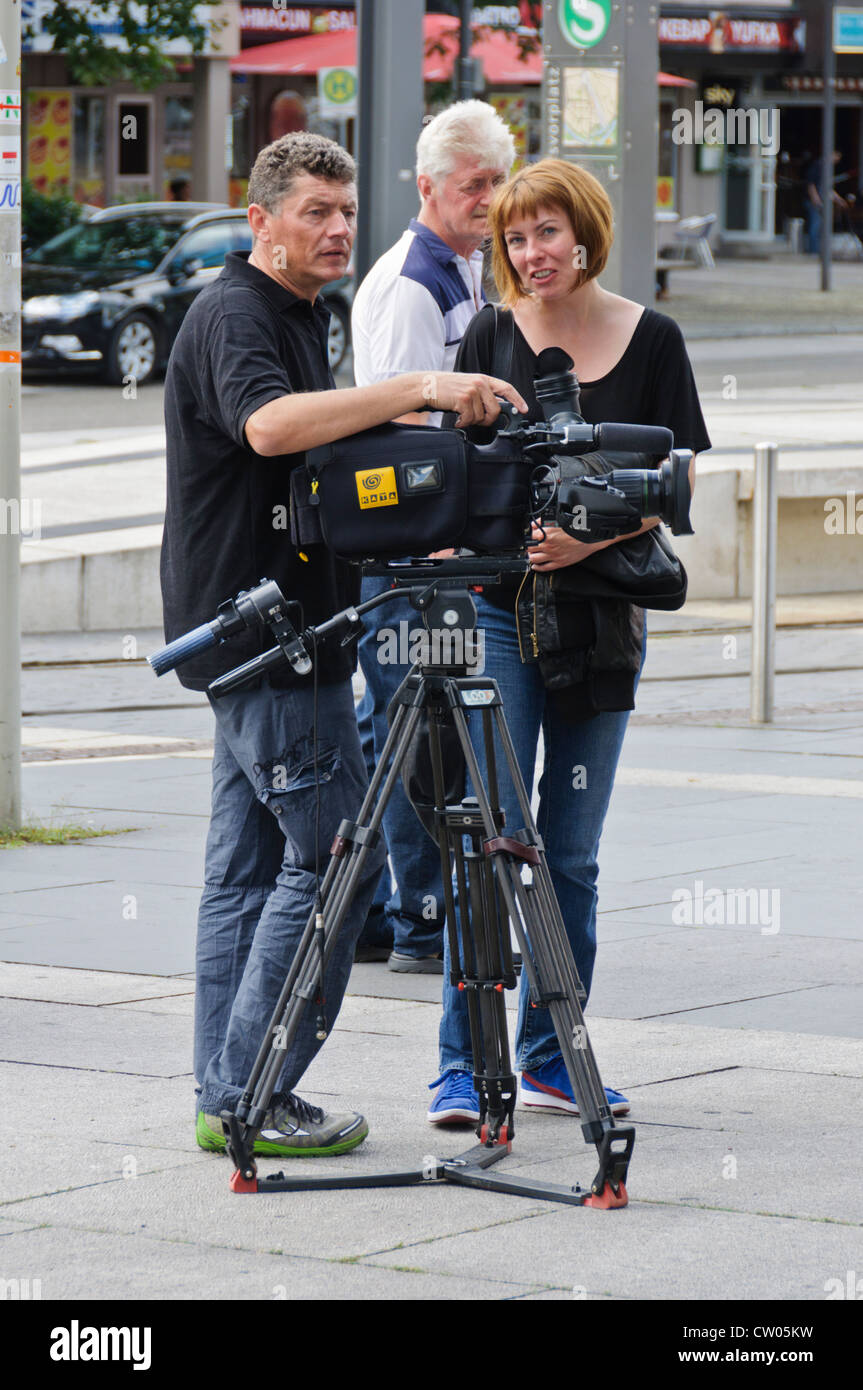 Television camera crew cameraman and female reporter with red hair, digital TV camera on professional tripod - Stock Image