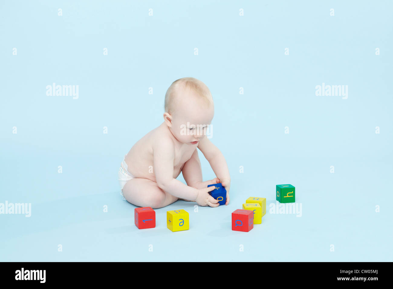 Baby boy playing with colored blocks - Stock Image