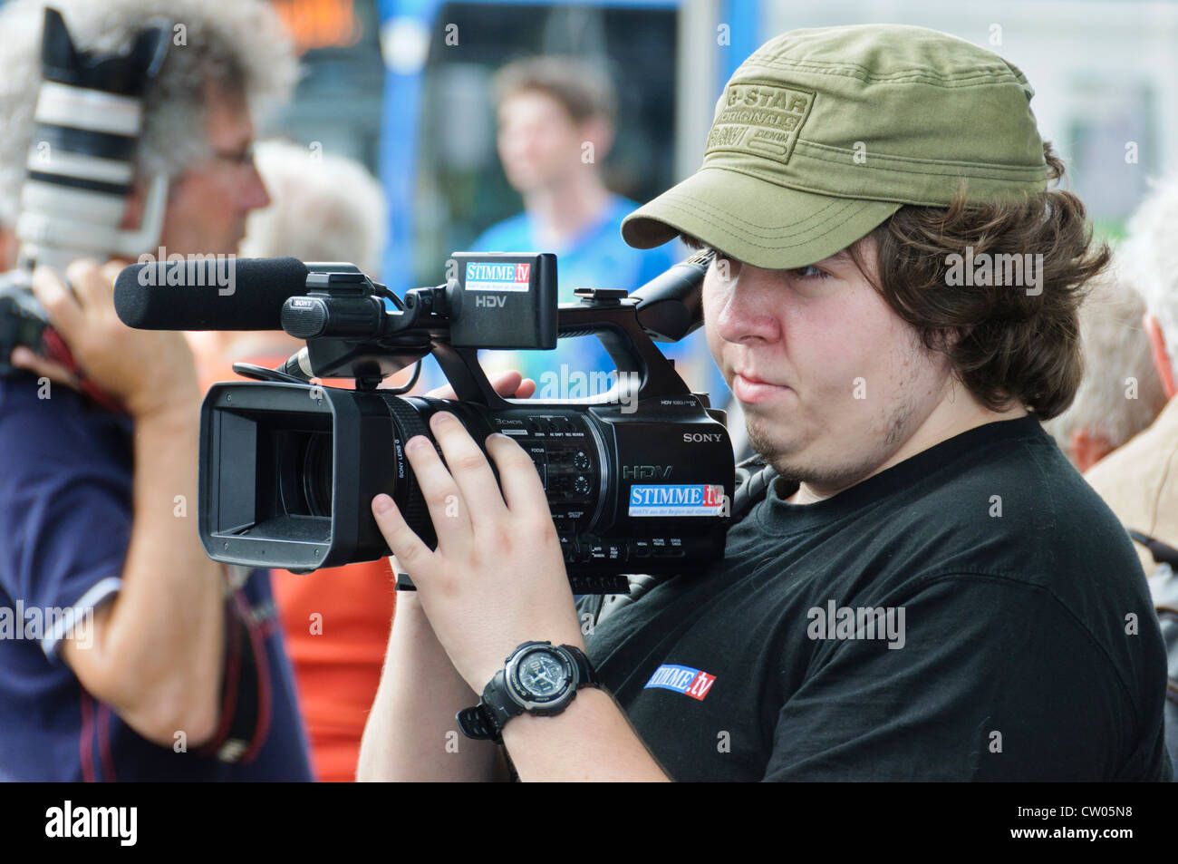 Overweight German cameraman from the regional broadcast station STIMME.TV shooting with semi professional Sony HDV - Stock Image