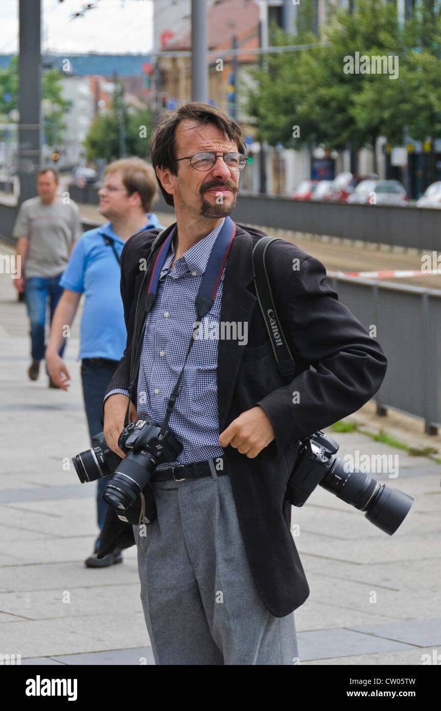 Professional photographer carries three CANON EOS DSLRs with zoom lenses around his neck - Stock Image