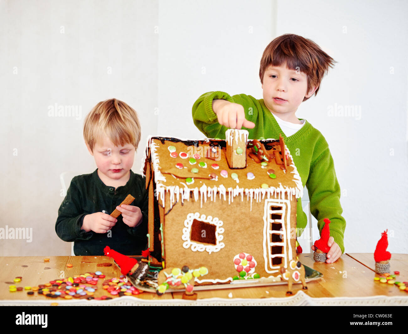 Boys decorating gingerbread house - Stock Image