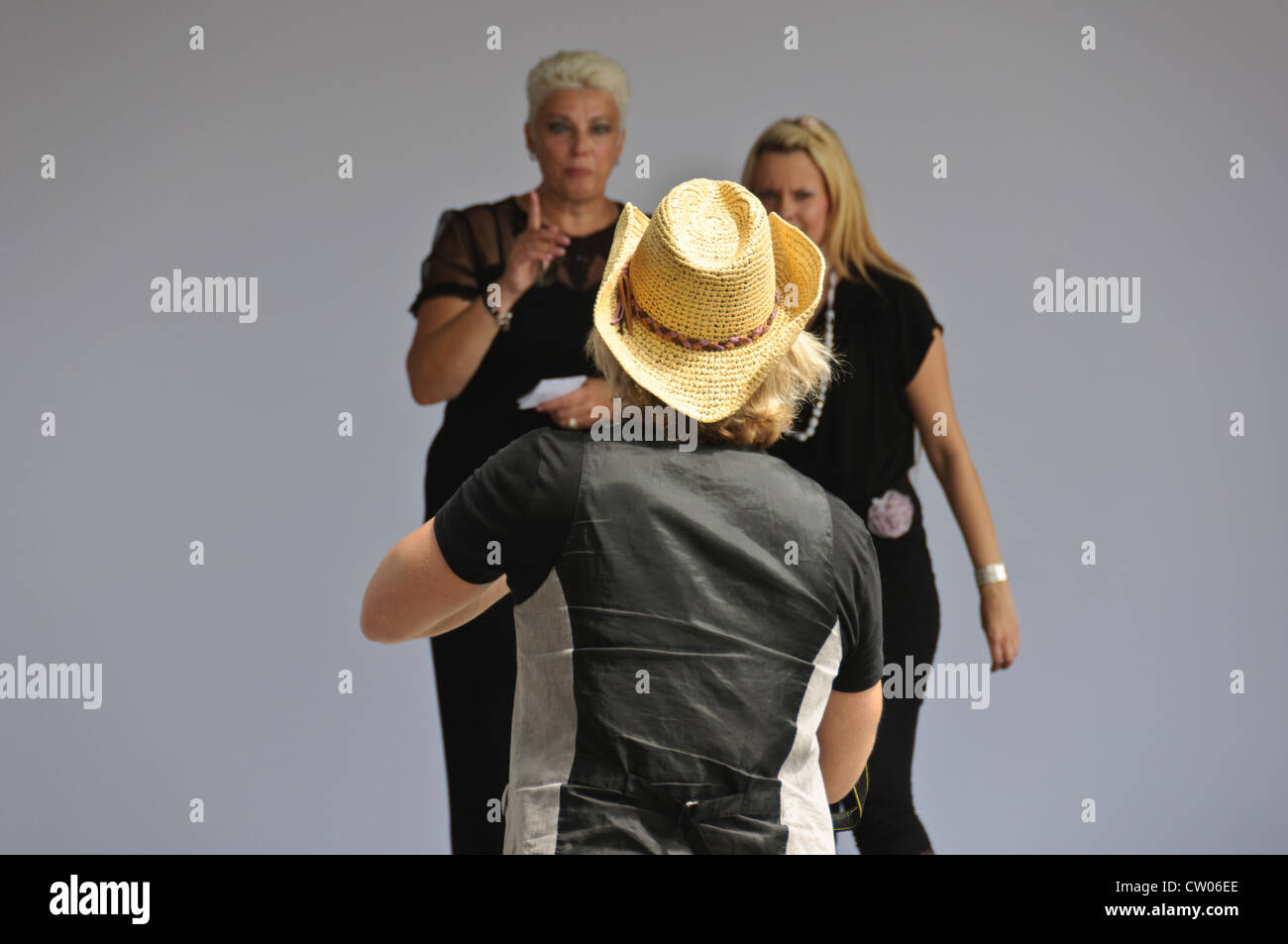 Man wearing straw cowboy hat Stetson style approaches two blond women - Stock Image