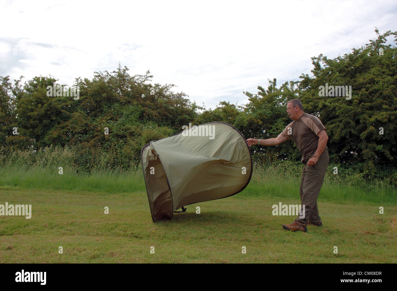 Alamy & Man throwing pop-up tent into the air - 4 of a series of 5 Stock ...