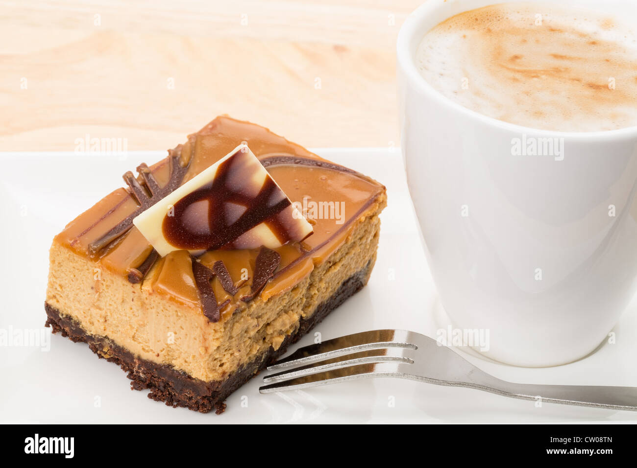 Slice of caramel cheesecake with a cup of coffee - studio shot - Stock Image